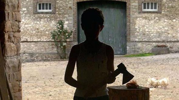 Junge mit Hackebeil in Hofeinfahrt, man sieht nur den Schattenriß (Filmverleih)