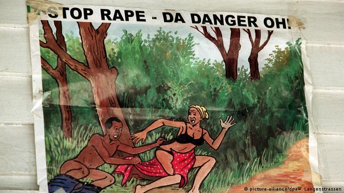 A poster shows a cartoon of a man jumping out and trying to attack a woman. The top of the poster reads 'stop rape'