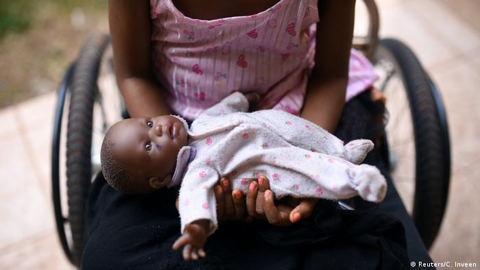 A five-year-old Sierra Leonean rape victim sits in a wheelchair with her doll and holds her doll towards the camera. Her face is out of frame.