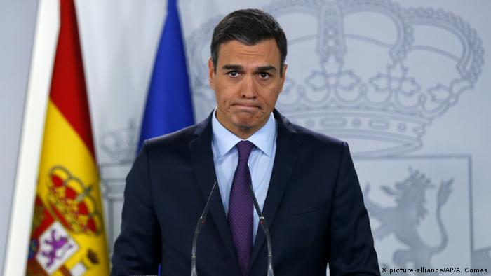 Pedro Sanchez looks befuddled while standing at a podium