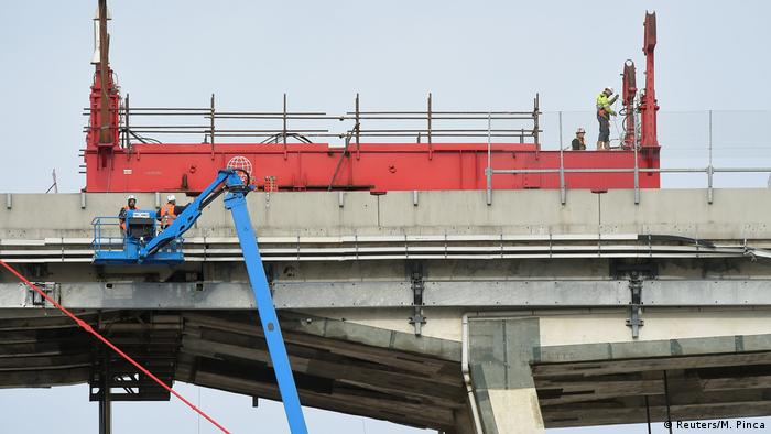 Construction workers in cranes dismantle the remnants of the collapsed Morandi Bridge in Genoa (Reuters/M. Pinca)
