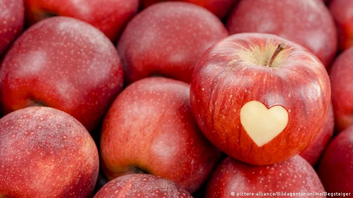 Red apple with heart carved into it.