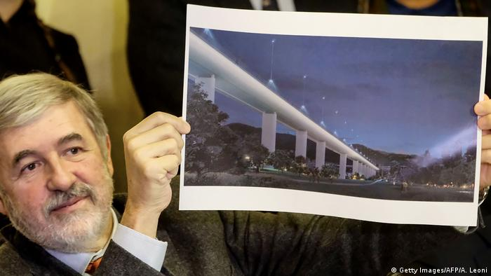 Genoa Mayor Marco Bucci holds up an artist rendition of the Renzo Piano bridge design (Getty Images/AFP/A. Leoni)