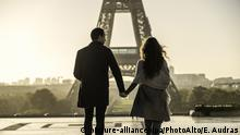 A couple walks in front of the Eiffel Tower (picture-alliance/dpa/PhotoAlto/E. Audras)