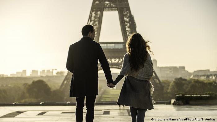 A couple walks in front of the Eiffel Tower