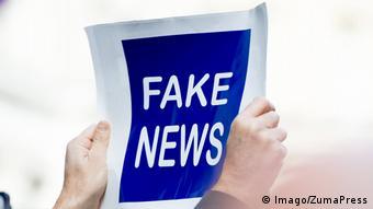 человек держит в руках плакат, на котором написано fake news