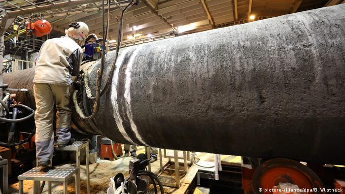 Рабочий ведет сварку труб газопровода