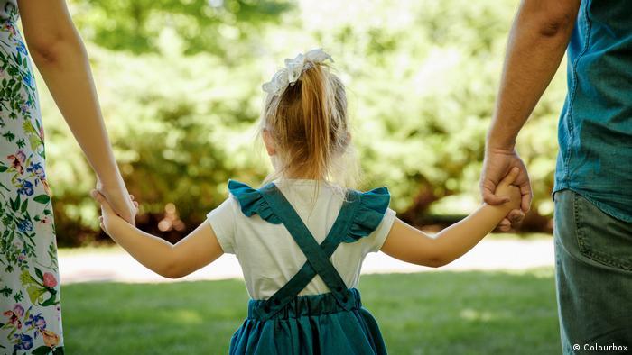 Девочка держит за руки женщину и мужчину