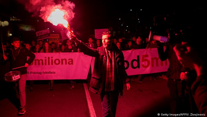 A red flare lights the way for the protest rally in Belgrade