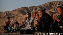 TURPAN, CHINA - SEPTEMBER 12: (CHINA OUT) A Uyghur family pray at the grave of a loved one on the morning of the Corban Festival on September 12, 2016 at a local shrine and cemetery in Turpan County, in the far western Xinjiang province, China. The Corban festival, known to Muslims worldwide as Eid al-Adha or 'feast of the sacrifice', is celebrated by ethnic Uyghurs across Xinjiang, the far-western region of China bordering Central Asia that is home to roughly half of the country's 23 million Muslims. The festival, considered the most important of the year, involves religious rites and visits to the graves of relatives, as well as sharing meals with family. Although Islam is a 'recognized' religion in the constitution of officially atheist China, ethnic Uyghurs are subjected to restrictions on religious and cultural practices that are imposed by China's Communist Party. Ethnic tensions have fueled violence that Chinese authorities point to as justification for the restrictions. (Photo by Kevin Frayer/Getty Images)