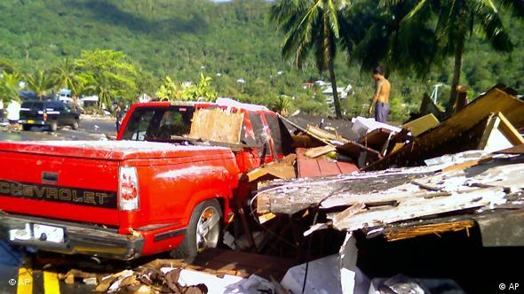 A pickup truck sits near a pile of rubble on the island of Samoa