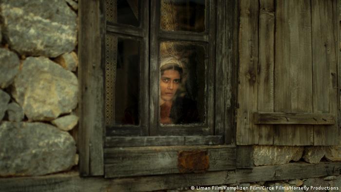 Filmszene aus A Tale of Three Sisters zeigt eine Frau aus dem Fenster einer einfachen Hütte blickend (Liman Film/Komplizen Film/Circe Films/Horsefly Productions)