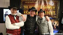 Three men stand together in western clothes at the Country Music Meeting Event in Berlin (DW/S. Sanderson)