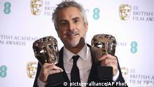 Director Alfonso Cuaron poses for photographers backstage with his Best Film and Best Director award for his film 'Roma' at the BAFTA awards in London, Sunday, Feb. 10, 2019. (Photo by Joel C Ryan/Invision/AP) |