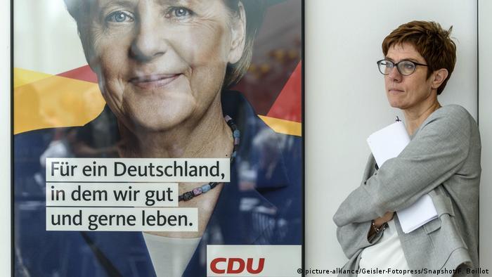 Annegret Kramp-Karrenbauer next to a poster of her predecessor Angela Merkel