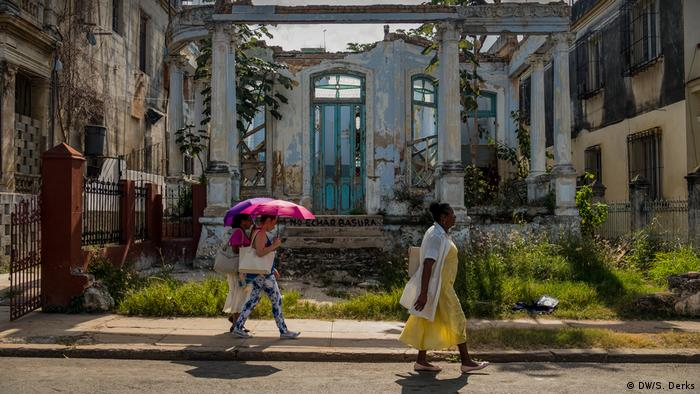 Women walk past the ruins of a house (DW/S. Derks)