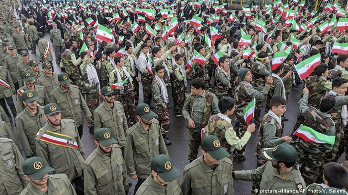 School students wave their national flags as Revolutionary Guard members arrive in Azadi