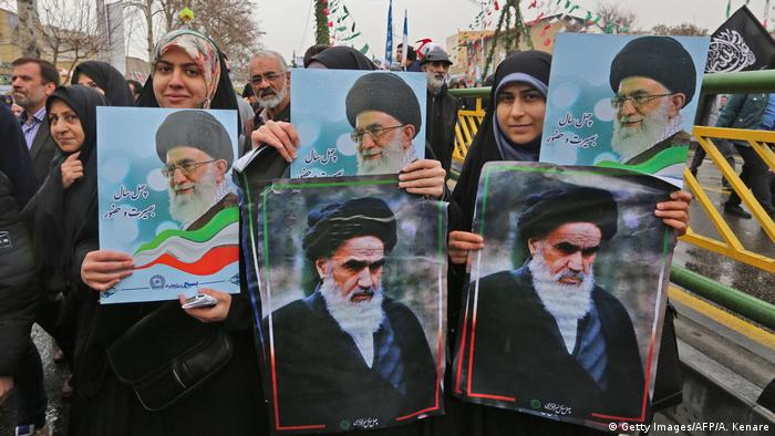 Iranian women pose with portraits of the country's Supreme Leader Ali Khamenei (top) and his predecessor and Islamic Revolution founder Ayatollah Ruhollah Khomeini