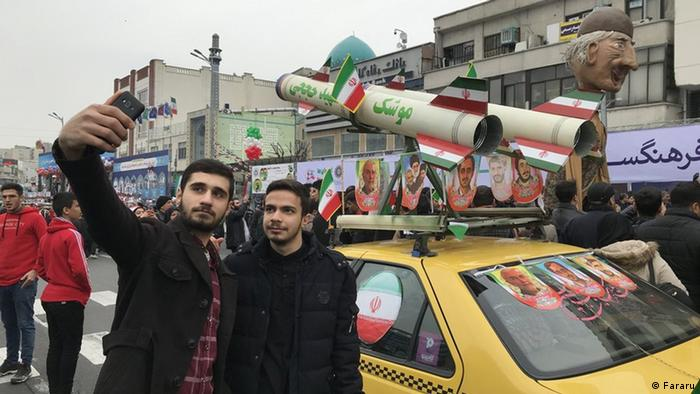 Two men take a selfie in front of a car with a missile sculpture on top