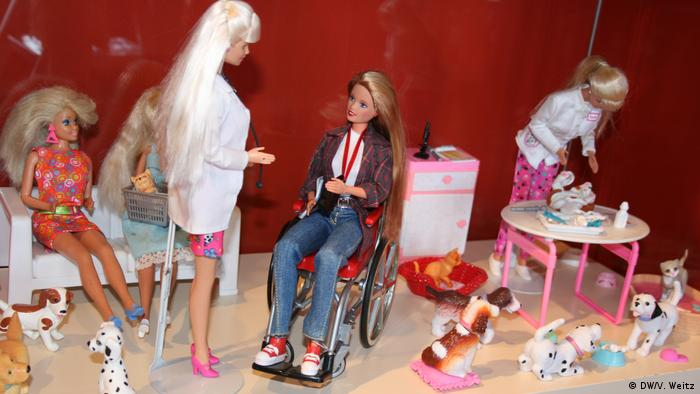 Barbies and accessories are staged