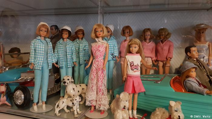Barbies stand on a shelf with miniature dogs