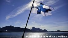 A Finnish flag flies from a ship on a body of water