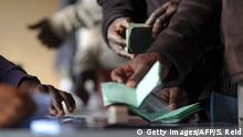 People show their passport prior to vote for the general elections, on May 7, 2014 at a polling station in Marikana. South Africans vote in their fifth democratic elections on May 7, seen as the biggest test yet for the ruling African National Congress, in power since the end of apartheid in 1994. AFP PHOTO/SKYLER REID (Photo credit should read Skyler Reid/AFP/Getty Images)