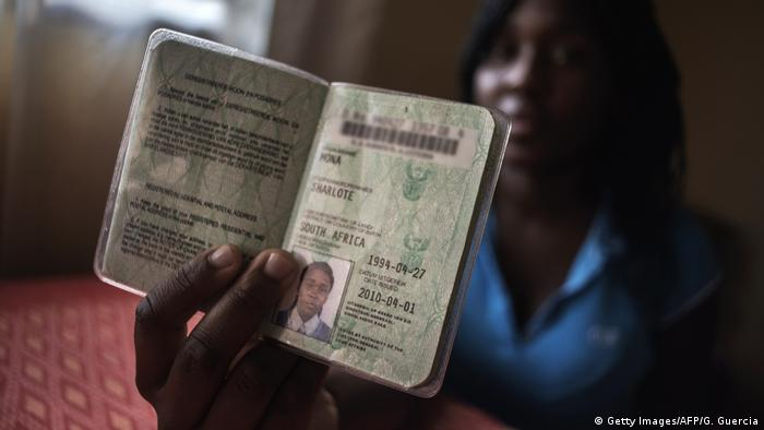 A South African woman holds up her passport to the camera