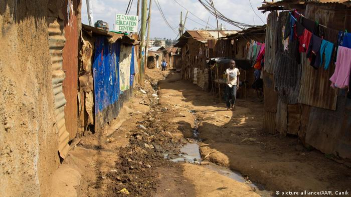 A dirt street in Nigeria's largest slum, Kiberia. A young boy looks towards the camera from the side of frame