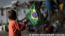 23.08.2018, Brasilien, Pacaraima:Ein Kind der ethnischen Gruppe Warao aus Venezuela hält die Fahne Brasiliens im Flüchtlingslager Janokoida. In dem armen brasilianischen Bundesstaat Roraima im Norden des Landes haben sich bislang über 50 000 Venezolaner niedergelassen. Wegen der schweren Wirtschafts- und Versorgungskrise in Venezuela kehren derzeit Hunderttausende ihrer Heimat den Rücken. Nach Angaben der UN haben bereits 2,3 Millionen Venezolaner das Land verlassen. Foto: Marcelo Camargo/Agencia Brazil/dpa +++ dpa-Bildfunk +++ |