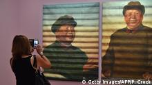 A woman takes a picture of Ai Weiwei's 'Mao' following the launch of the joint exhibition 'Andy Warhol/Ai Weiwei' in Melbourne on December 10, 2015. Ai Weiwei on December 10 said he believes his activism is helping to change China and the price he has paid for speaking out was worth it. AFP PHOTO/Paul Crock RESTRICTED TO EDITORIAL USE, MANDATORY MENTION OF THE ARTIST UPON PUBLICATION, TO ILLUSTRATE THE EVENT AS SPECIFIED IN THE CAPTION / AFP / PAUL CROCK (Photo credit should read PAUL CROCK/AFP/Getty Images)