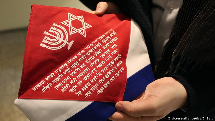 A depiction of a Menorah and Star of David with Hebrew writing on red fabric