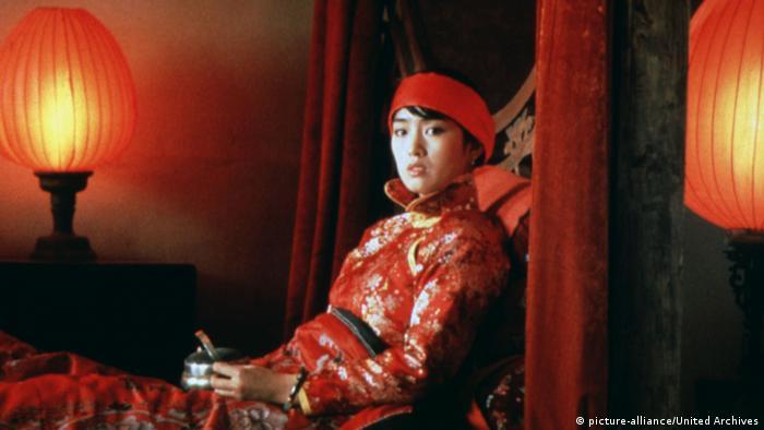 Filmszene aus Die Rote Laterne (1991), eine Frau in rotem Kinomo sitzt neben roten Laternen