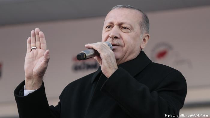 Recep Tayyip Erdogan speaking with a microphone