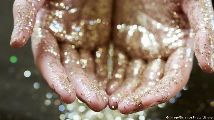 Mão segura glitter dourado
