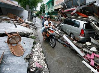 Residents ride a motorcycle in a neighborhood damaged by an earthquake in Padang, Indonesia