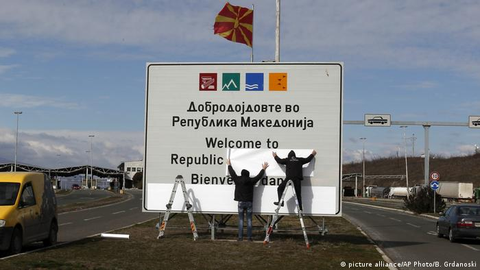 Workers replace signage at the North Macedonia border to Greece