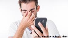 ILLUSTRATION - Ein Mann haelt am 14.07.2017 in einem Studio in Hamburg ein Smartphone in der Hand und faesst sich an die Augen (gestellte Szene). Foto: Christin Klose | Verwendung weltweit