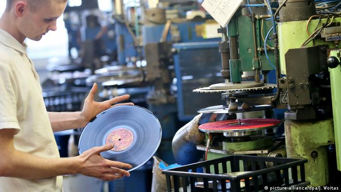A man holding a vinyl record (picture-alliance/dpa/J. Woitas)
