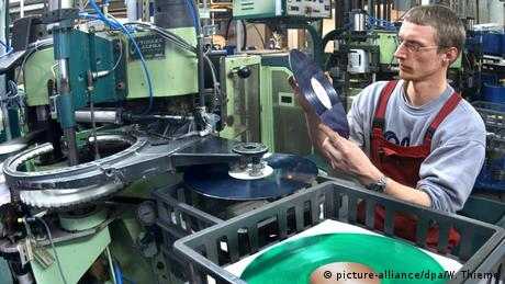 A worker inspecting a vinyl record (picture-alliance/dpa/W. Thieme)