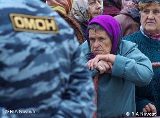 Бабушка в платке смотрит на омоновца