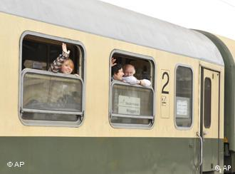 People wave from a train