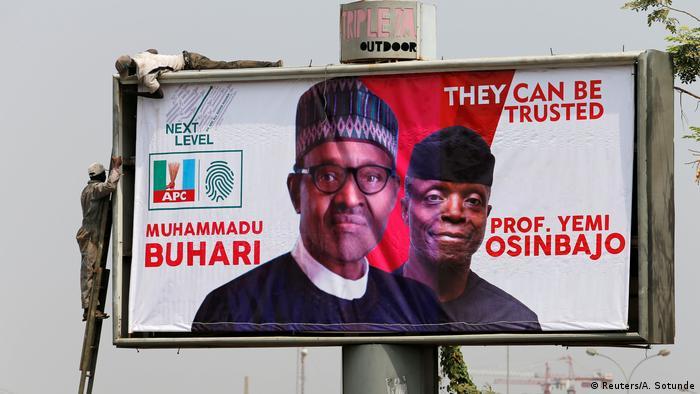 Workers fix an election campaign billboard depicting Nigerian President Muhammadu Buhari and his Vice President, Yemi Osinbajo, in Abuja, Nigeria