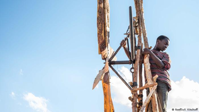 Film still from The Boy Who Harnessed the Wind - a boy on a wooden construction