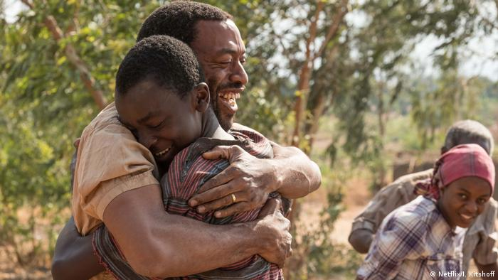 Film still: The Boy Who Harnessed the Wind - Chiwetel Ejiofor and Maxwell Simba hugging