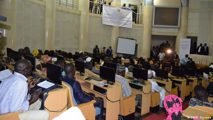 Members of parliament in Guinea Bissau sit in parliament in front of computer screens, facing away from the camera and towards the front of the room