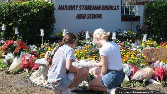 Two girls lay down notes and flowers at a memorial in front of Marjory Stoneman Douglas High School.