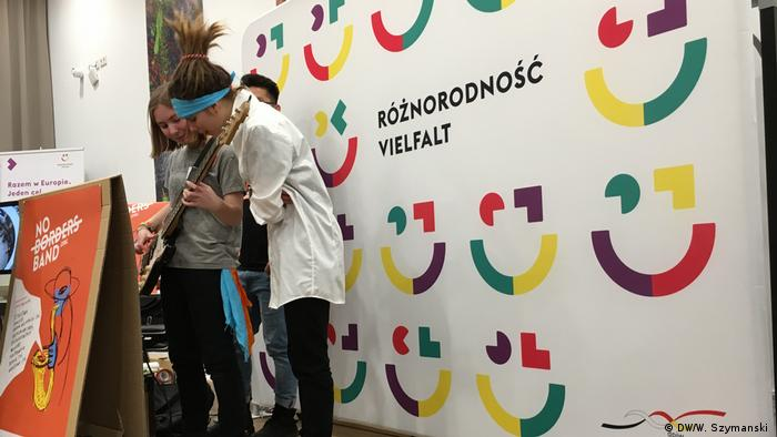 Young musicians stand in front of a poster promoting German-Polish ties