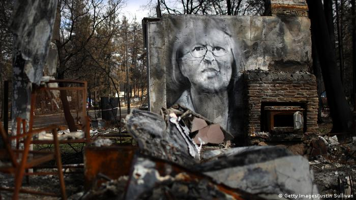 A mural of a woman on a destroyed house in Paradise