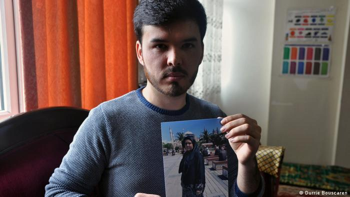 A young man holds up a photograph of his mother